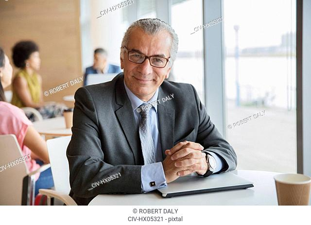 Portrait confident businessman in cafeteria