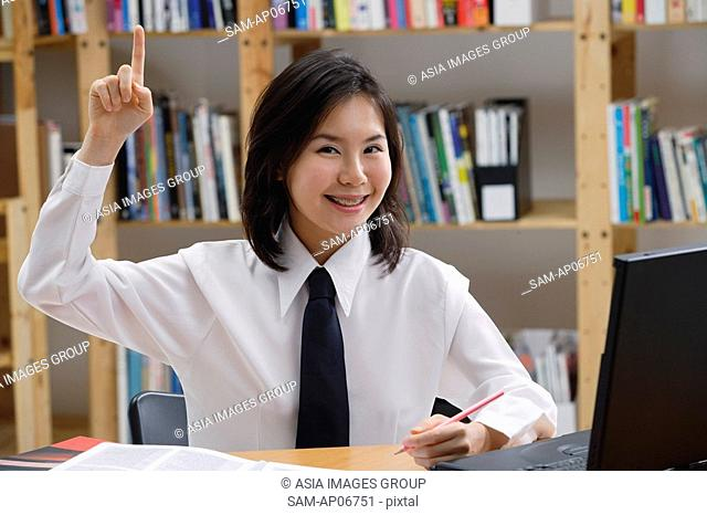 Young woman in library, hand raised, smiling