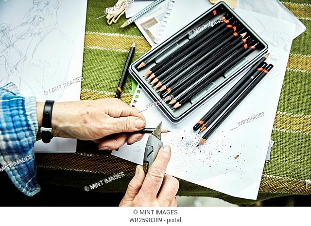 A person using a sharp blade, a craft knife, to sharpen lead pencils. Sketches on paper