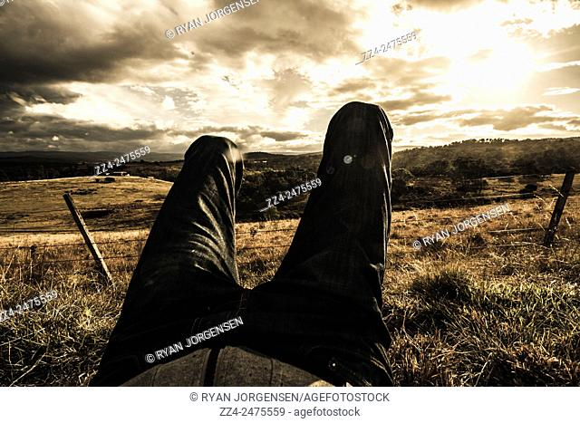 Horizontal first person POV concept of a travelling man kicking back while relaxing in a autumn farmyard meadow. Cranbrook, Tasmania, Australia