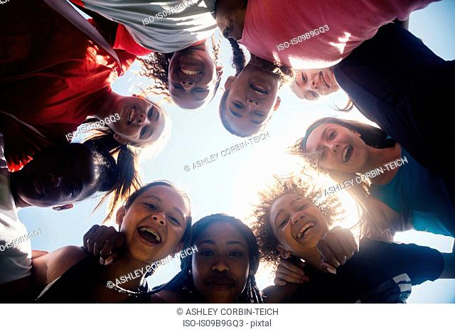 Low angle view of schoolgirl soccer team huddled in circle