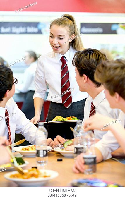 High school students eating lunch and talking in school cafeteria