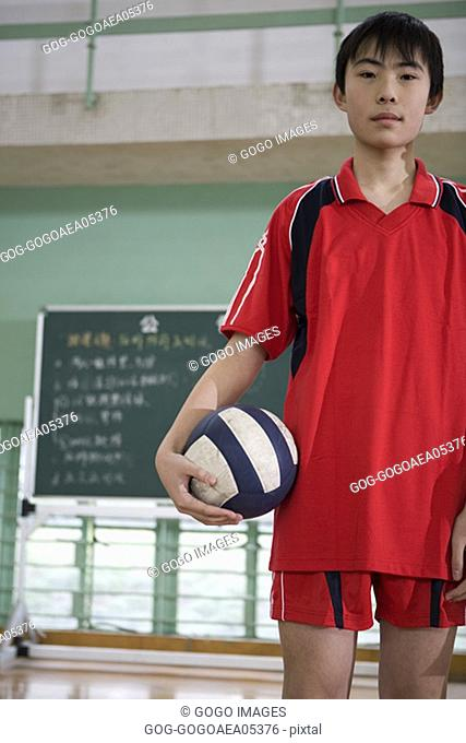 Male volleyball player holding volleyball