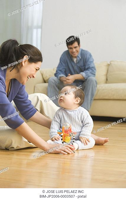 Hispanic parents smiling at baby on floor