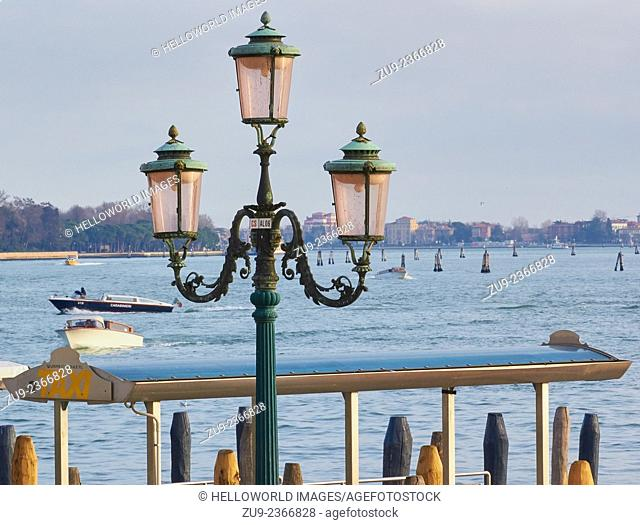 Old fashioned decorative street lamp next to a water taxi stop on Venice Lagoon, Veneto, Italy, Europe