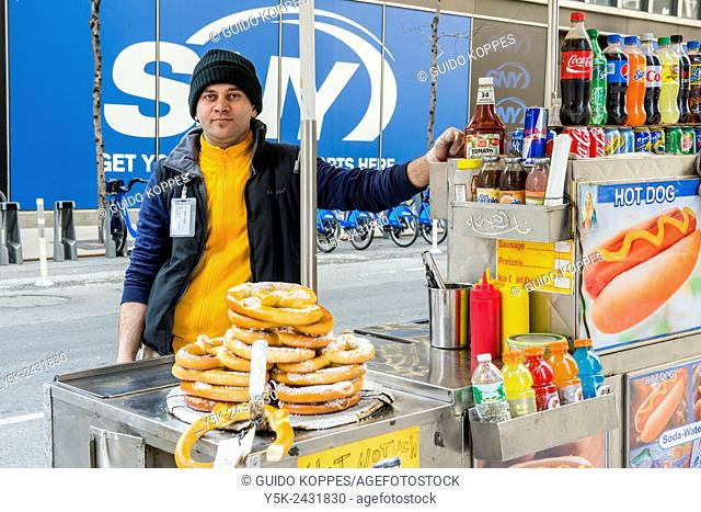 New York, USA. Arabic immigrant to the United States selling Hot Dogs & Pretsels from his mobile stand, Down Town Manhattan