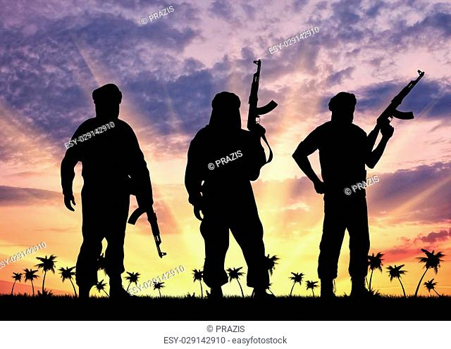 Concept of terrorism. Silhouette of three terrorists with a weapon against a background of sunset and palm trees
