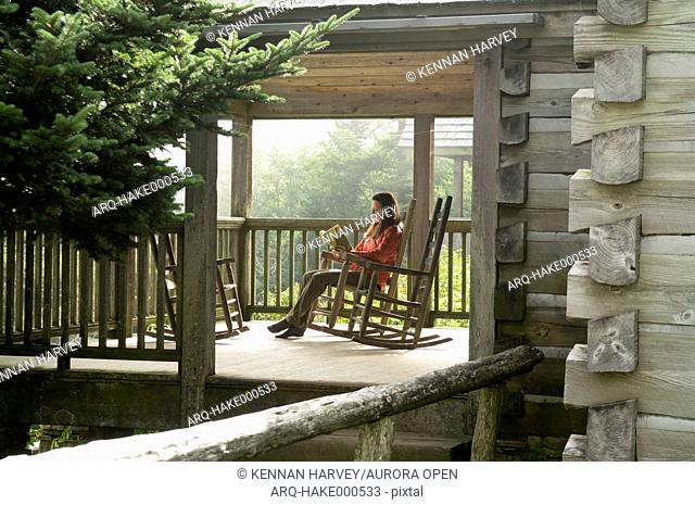 A woman in a rocking chair reading on the porch of a cabin at Leconte Lodge, Mount Leconte, Great Smoky Mountain National Park, Gatlinburg, Tennesee