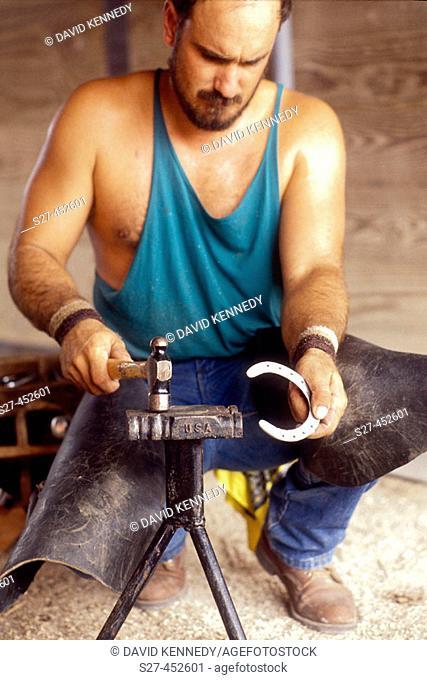 A blacksmith works on a horseshoe