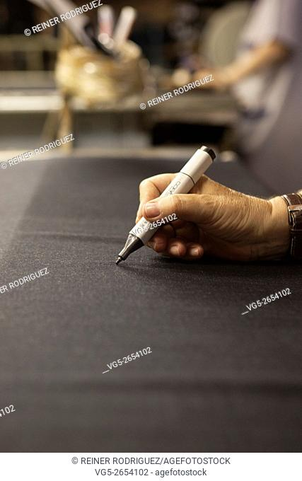 marking and repairing quality problems of a fabric. production of fine woolen fabrics for suits - in a factory in Sabadell, Spain