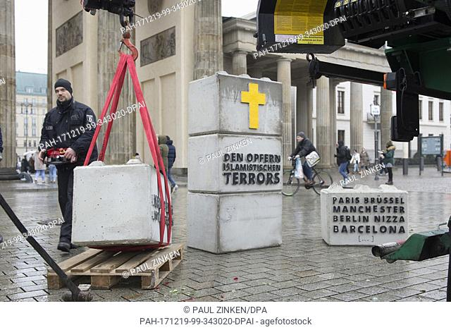 Police officers use a crane to remove stones with inscriptions, which were placed in front of the Brandenburg Gate by the right-wing Identity Movement