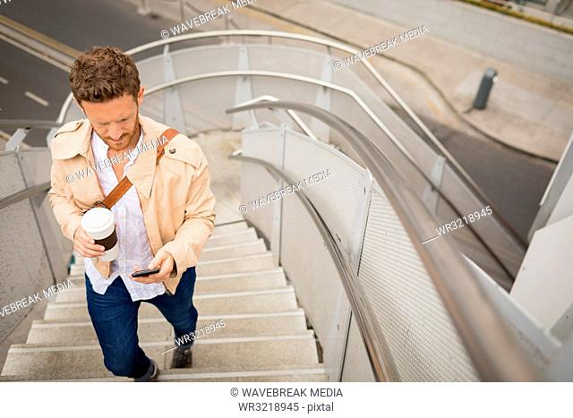 Man walking up stairs while using mobile phone
