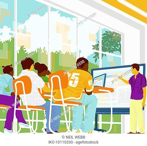 Students watching teacher at screen in modern classroom