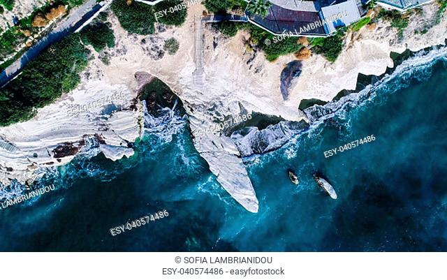 Aerial view of landmark big white chalk rock at Governor's beach, Limassol, Cyprus. The steep stone cliffs and deep blue sea waves crushing in coves and dark...