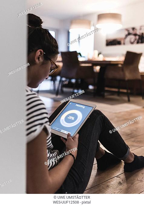 Woman using tablet with heating control function at home
