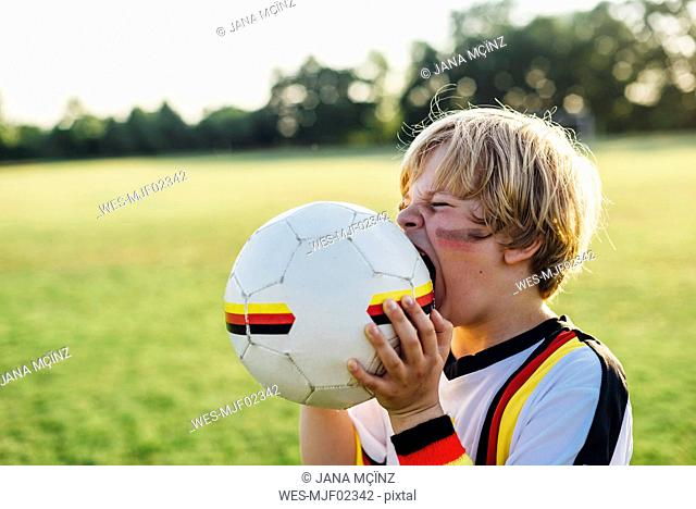 Boy with face paint and German football shirt, biting soccer ball