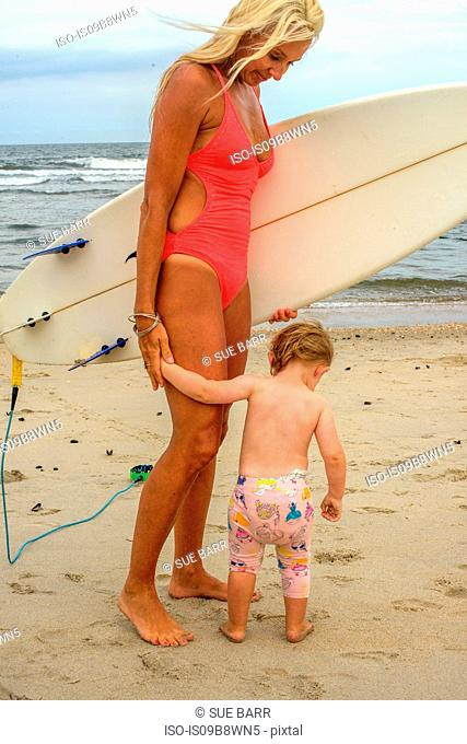 Woman carrying surfboard on beach with toddler daughter, Asbury Park, New Jersey, USA
