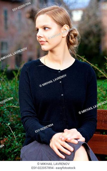 Pretty young blond woman sitting on bench