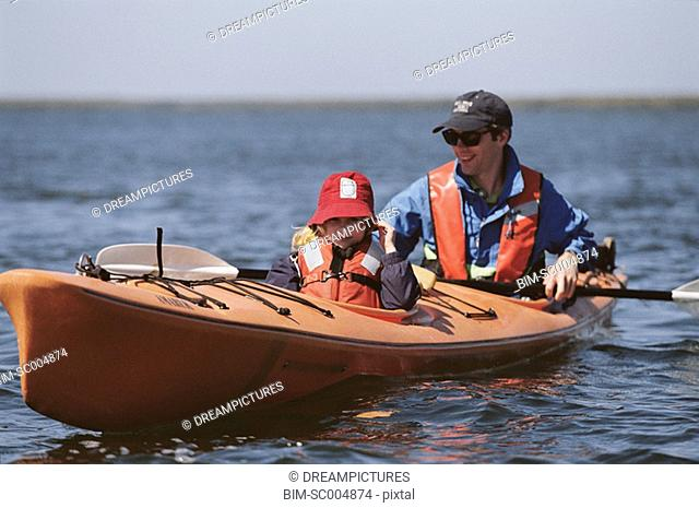 Father and young daughter in kayak wearing life-jackets