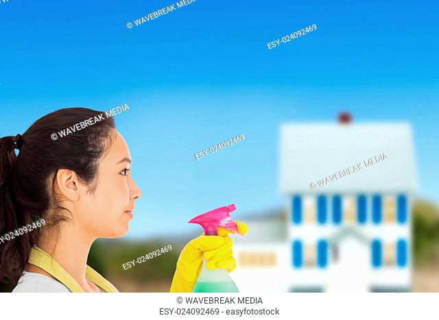 Composite image of woman spraying cleaning product