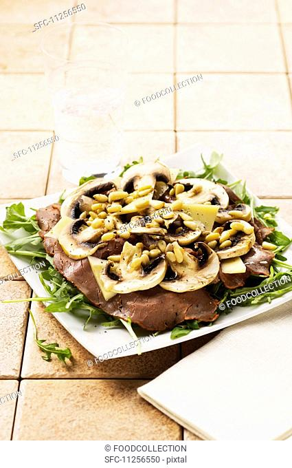 Roast beef with mushrooms and pine nuts on rocket
