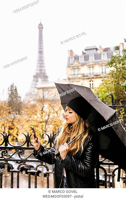 France, Paris, young woman using her smartphone with the Eiffel Tower in the background