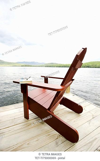 Book and chair on lake side dock