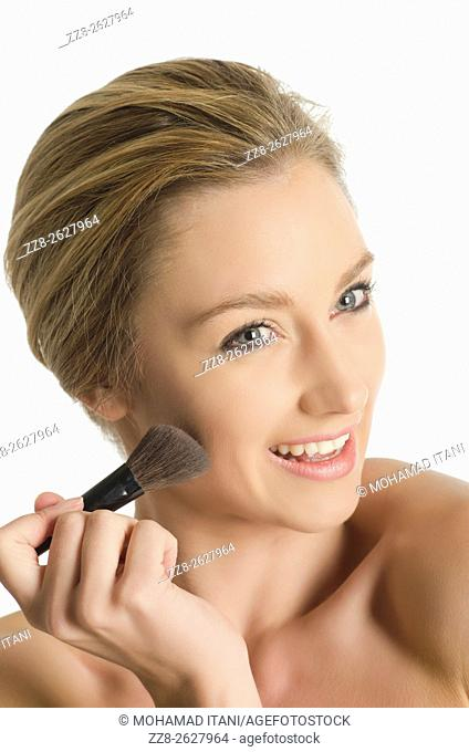 Beautiful young woman applying blusher to her face
