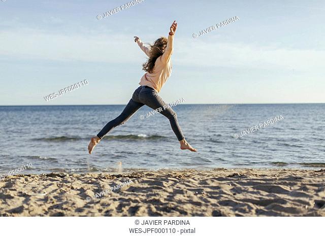 Spain, Lleida, woman jumping on the beach