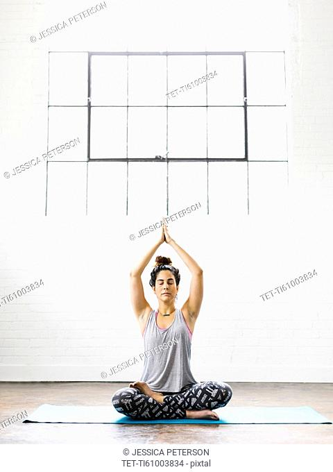 Woman meditating on exercise mat