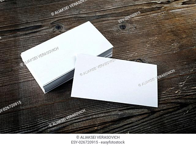 Photo of blank white business cards on a dark wooden background. Mock-up for branding identity. Blank template for design presentations and portfolios