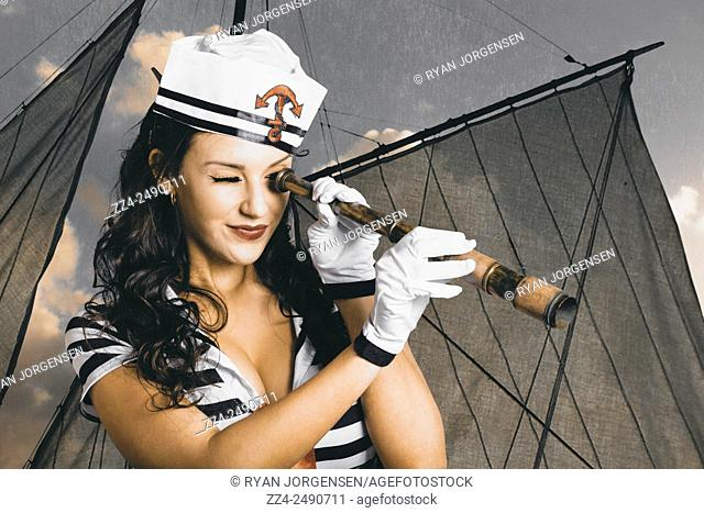 Vintage beauty photo of a shipshape maritime sailor woman holding retro telescope while on watch from the observation deck. Scouting deckhand