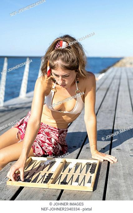 Young woman playing Blackgammon on pier