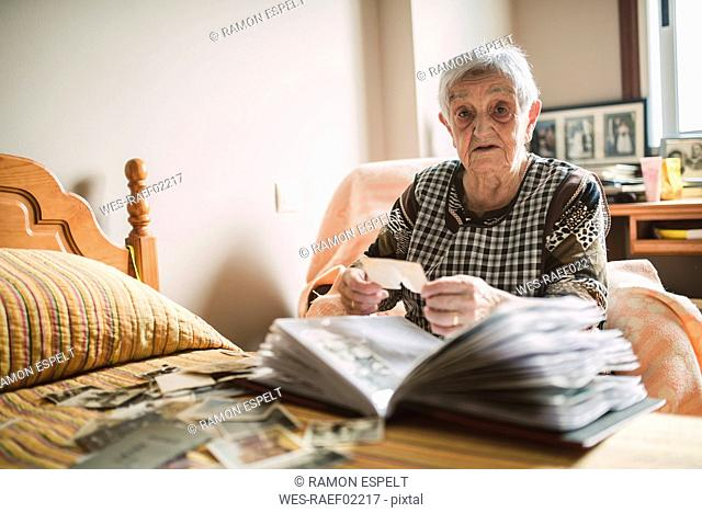 Portrait of senior woman adding old photos to a photo album at home