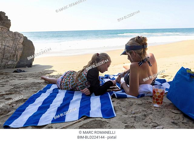 Caucasian mother and daughter playing backgammon on beach