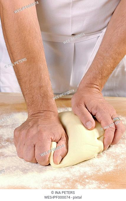 Hands of a man kneading pasta dough for home-made tortelloni