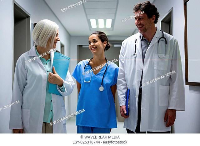 Doctors and surgeon interacting in corridor