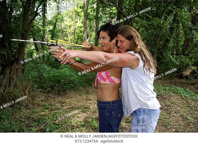 Woman Helping Friend Shoot Arrow With Slingshot