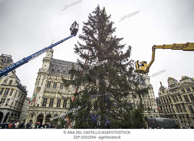 Brussels, Belgium. People visit The Grand Place or Grote Markt Brussels while with cranes the Christmas tree is mounted