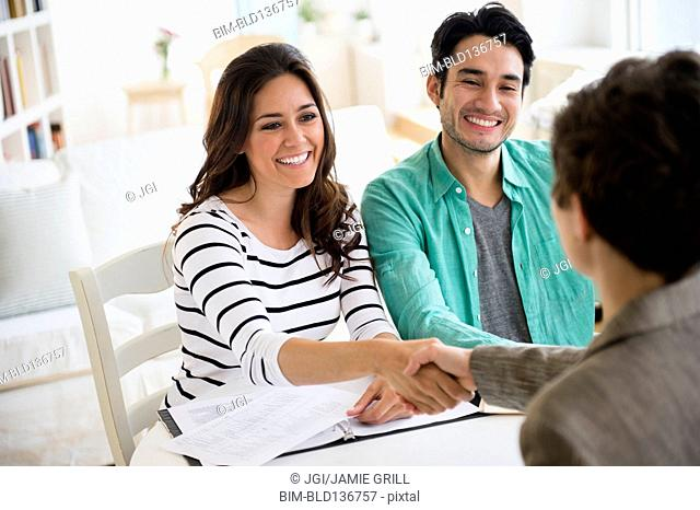 Couple shaking hands with financial adviser