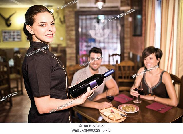 Waitress in bar ready to serve wine to a couple