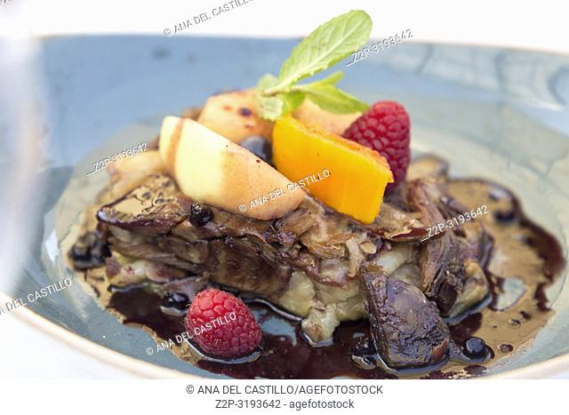 Duck with fruits on blue plate Spain