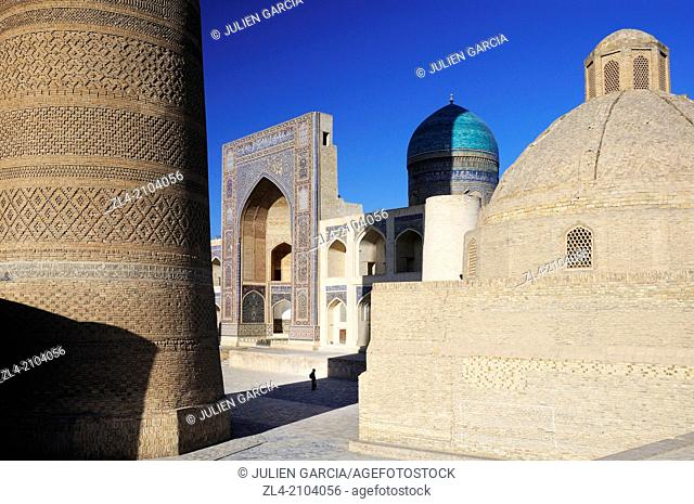 Silhouette in front of Mir-i-Arab Madrasa with Kalon minaret in the foreground. Uzbekistan, Bukhara