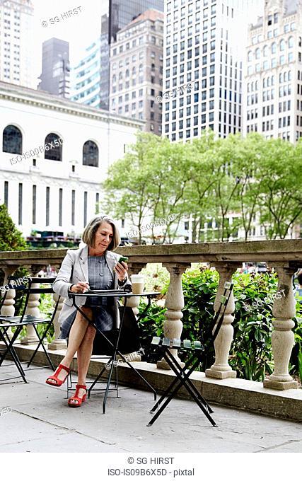 Businesswoman working on balcony, New York, USA