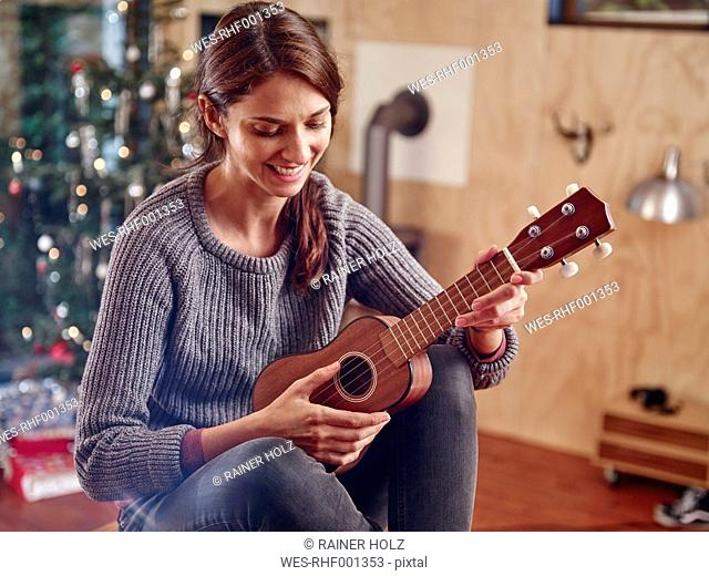 Woman playing ukulele in front of Christmas tree