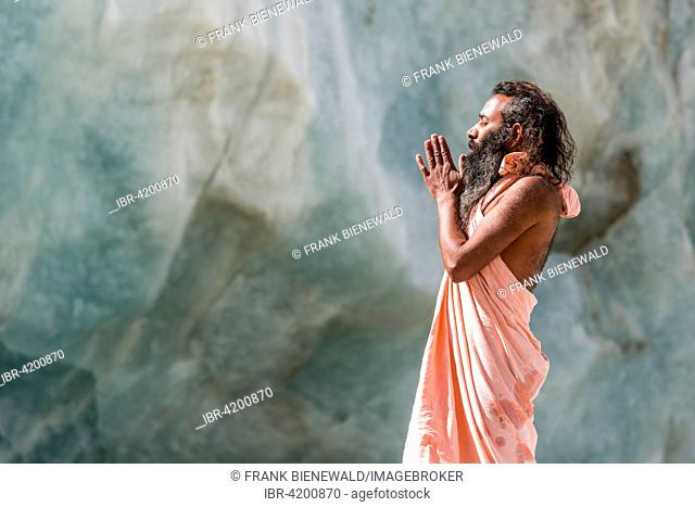 A Sadhu, holy man, is standing and praying on a block of ice at Gaumukh, the main source of the holy river Ganges, Gangotri, Uttarakhand, India