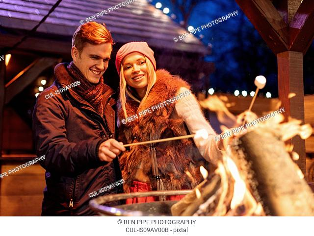 Young couple toasting marshmallows at xmas festival in Hyde Park, London, UK