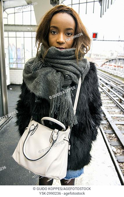 Paris, France. Urban portrait of a young adult, black woman just after commuting by subway, wearing modern fashion that defines her individual identity