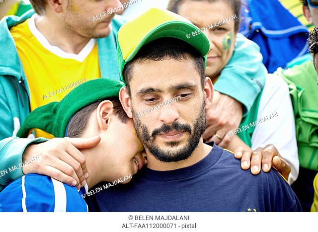 Brazilian football fans consoling each other at match