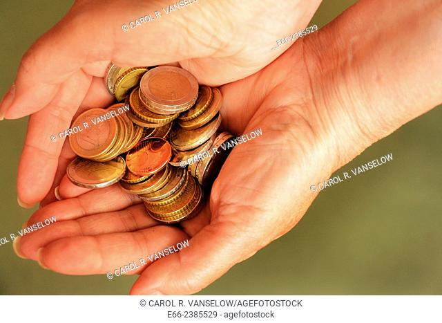 Euro coins in woman's hands